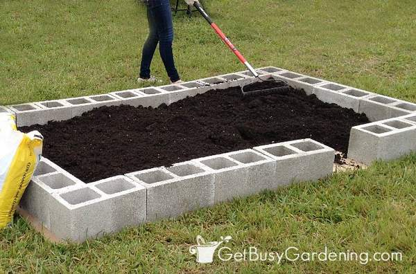 Fill the concrete block beds with quality soil for raised beds