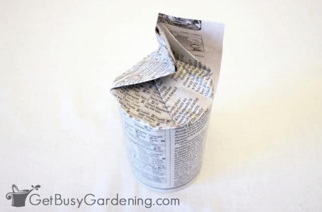 Newspaper folded around the bottom of a can
